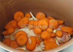 Сверху на мясо сложите лук и морковь