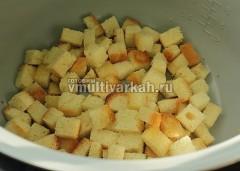 Достаньте чеснок, сложите нарезанный кубиками хлеб и выпекайте 20 минут