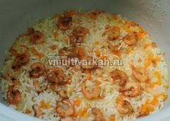 За 5 минут до готовности плова выложите креветки к рису и овощам