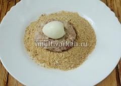 На тарелку высыпаю сухари, выкладываю фарш и вареное яйцо