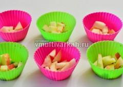 Формочки смазать маслом и выложить на дно яблоки