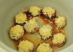 Через 20 минут выложить натертый сыр сверху на грибочки и влить воду, включить тот же режим на 15 минут