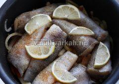 Сверху выкладываем тушки рыбы и дольки лимона