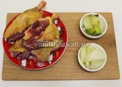 Разделите утку на порционные куски, нарежьте крупно лук и яблоки