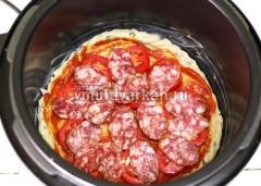 Раскатанное тесто уложите в чашу, смазанную маслом, намажьте томатной пастой и выложите салями с помидорами