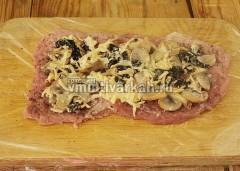 Мясо посыпьте солью и перцем, выложите начинку