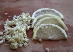 Лимон нарежьте дольками, чеснок порубите мелко
