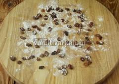 Когда тесто готово, посыпьте стол или доску мукой, рассыпьте промытый изюм