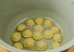 Мультиварку установите в режим Мультиповар 160 градусов, влейте ложку масла и выложите пельмени в 1 ряд