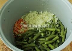 В чашу налейте масло, выложите лук, морковь и полуготовую спаржевую фасоль